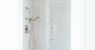 Small walk in shower features gray subway tiles on ceiling and walls lined with ...