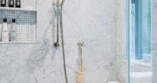 Fantastic walk-in shower features ceiling and walls clad in grey marble fitted w...