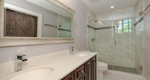 Immaculately-designed, transitional master bathroom featuring a large double van...